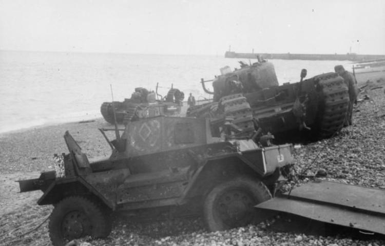 Daimler Dingo armoured car and two Churchill tanks bogged down on the shingle beach