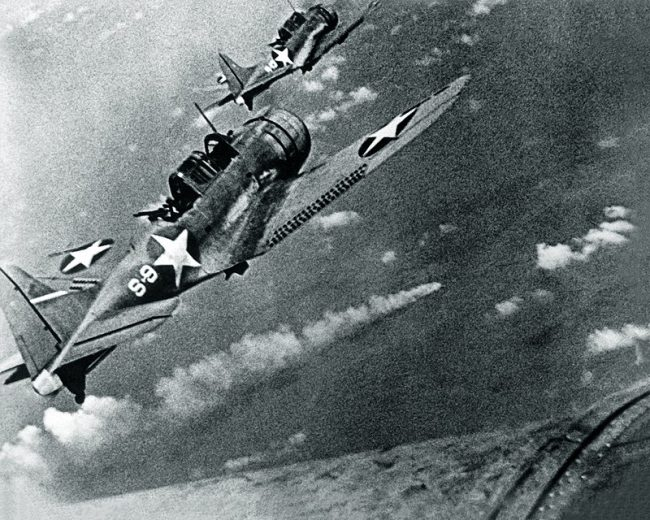 U.S. Navy Douglas SBD-3 'Dauntless' dive bombers from scouting squadron VS-8 from the aircraft carrier USS Hornet (CV-8) approaching the burning Japanese heavy cruiser Mikuma to make the third set of attacks on her, during the Battle of Midway, 6 June 1942.