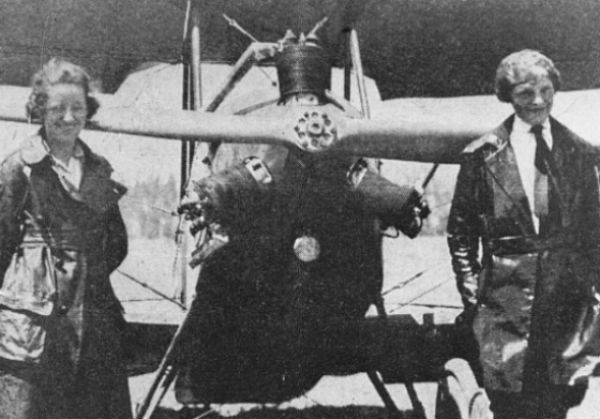 Amelia Earhart and Neta Snook stood in front of a plane