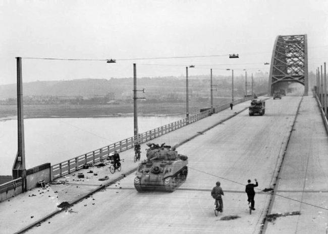 British tanks of XXX Corps cross the road bridge at Nijmegen.