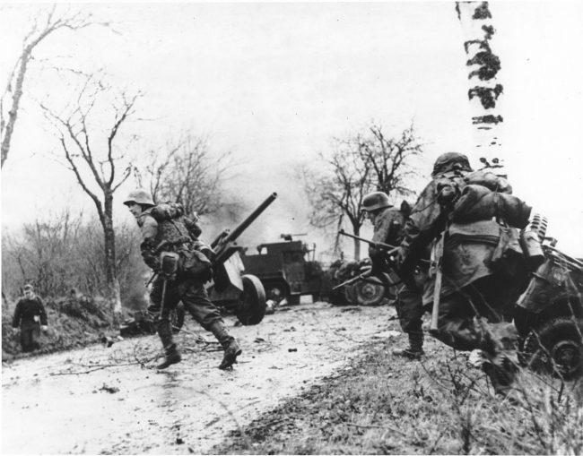 German troops advancing past abandoned American equipment
